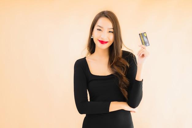 クレジットカードでの美しい若いアジア女性の肖像画