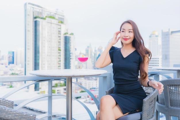 Женщина портрета красивая молодая азиатская наслаждается с стеклом питья коктеилей