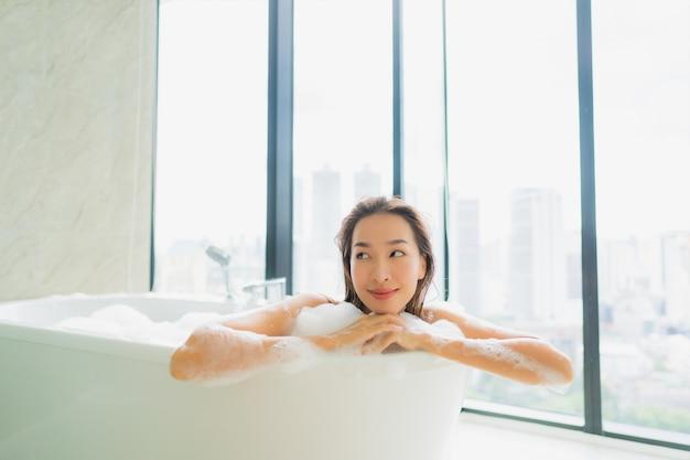 Женщина портрета красивая молодая азиатская ослабляет и отдыхает в ванне