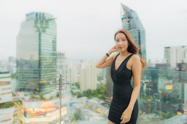 肖像画の美しい若いアジア女性はリラックスして屋上にレストランをお楽しみください