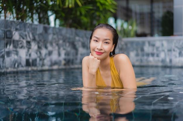 美しい若いアジア女性の肖像画は、スイミングプールの周りのレジャーをリラックスします。