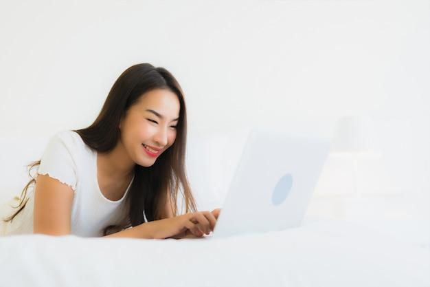 肖像画の美しい若いアジア女性はベッドの上のコンピューターのラップトップを使用します