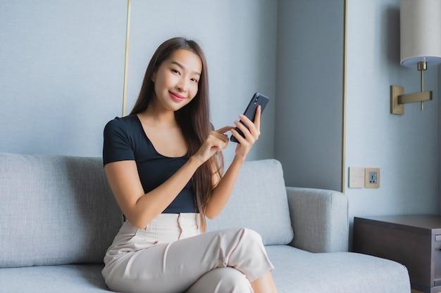 肖像画の美しい若いアジア女性はリビングルームエリアのソファーにスマートな携帯電話を使用します。