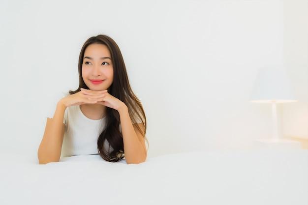 肖像画の美しい若いアジア女性は白い枕毛布が付いているベッドで幸せな笑顔をリラックスします。