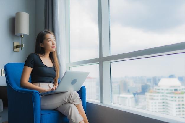 肖像画の美しい若いアジアの女性はリビングルームエリアのソファーにラップトップを使用します。