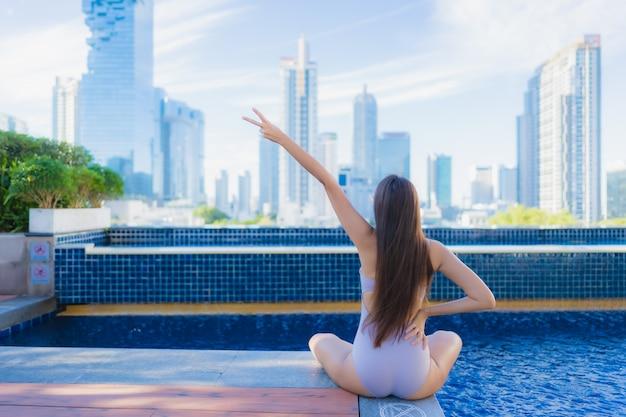 Женщина портрета красивая молодая азиатская ослабляет отдых наслаждается вокруг открытого бассейна