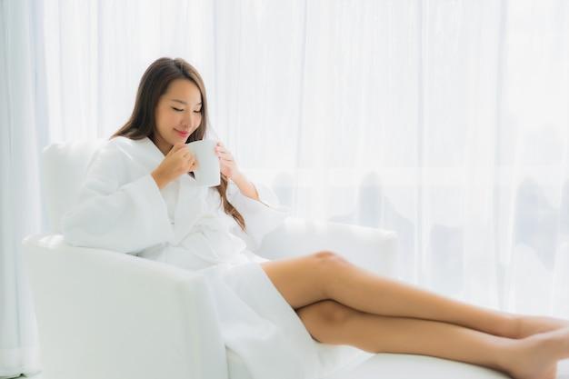肖像画の美しい若いアジア女性はソファの上のコーヒーカップで幸せな笑顔をリラックスします。