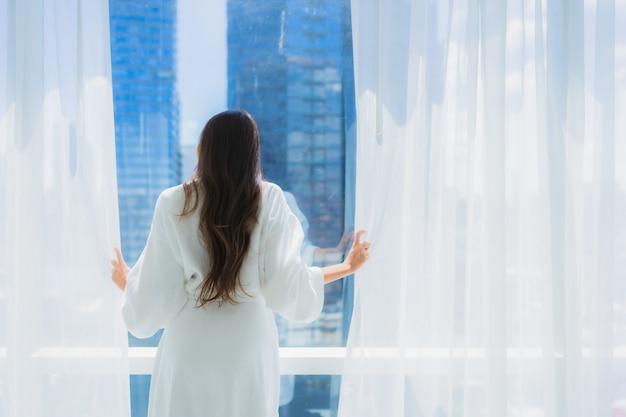 美しい若いアジアの女性の肖像画は、ビューの窓の外を見てください。