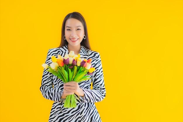 Улыбка женщины портрета красивая молодая азиатская счастливая с цветком на желтом цвете