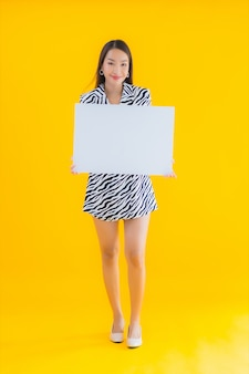 Улыбка женщины портрета красивая молодая азиатская с афишей выставки пустой белой на желтом цвете
