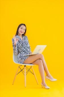 肖像画の美しい若いアジア女性は黄色のラップトップコンピューターを使用します。