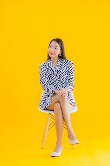 肖像画の美しい若いアジア女性は黄色のアクションで椅子に座る