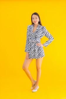Улыбка женщины портрета красивая молодая азиатская счастливая с действием на желтом цвете