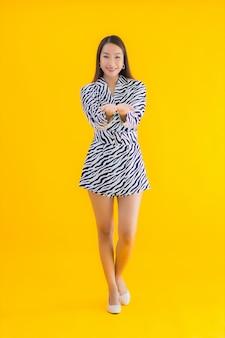肖像画の美しい若いアジア女性は黄色のアクションに満足して笑顔します。