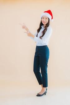 肖像画の美しい若いビジネスアジア女性はクリスマスの帽子を着用します。