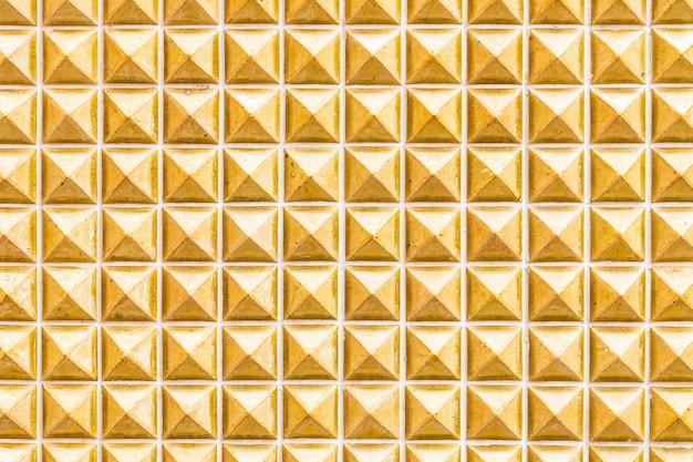 背景のための黄色の大理石のタイルの壁のテクスチャ