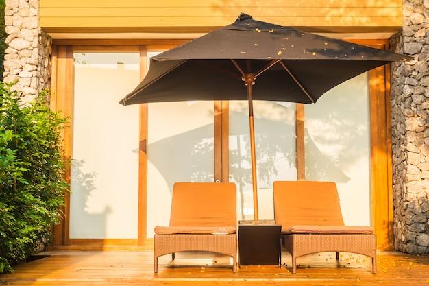 傘とスイミングプールの周りの椅子