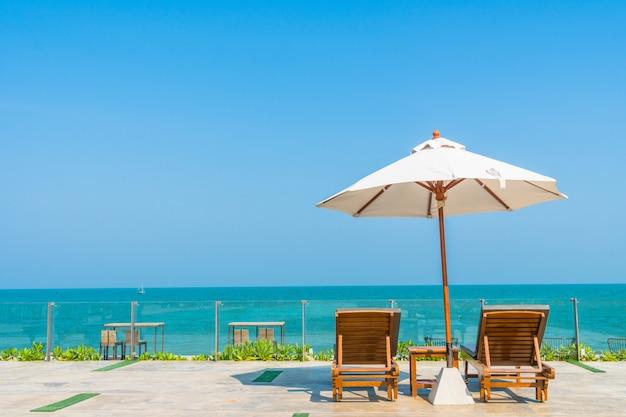 美しい傘とホテルとリゾートのプールの周りの椅子