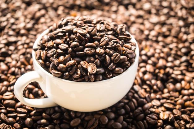 白いカップに茶色のコーヒー豆