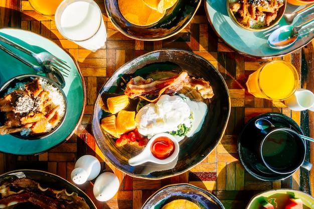 健康的な朝食と卵ベーコンのパンケーキオレンジジュース牛乳パンとコーヒーセット