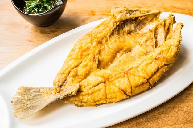 スパイシーで甘いソースの白いプレートの揚げスズキ魚