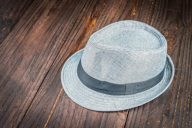 木製の背景にビーチ帽子