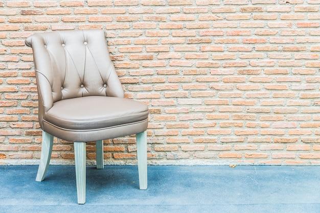 レンガの壁の背景に高級革製の椅子