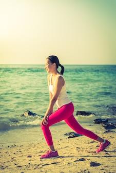 Действие йоги молодой женщины на пляже