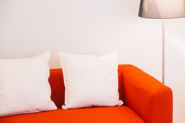 枕と光のランプが付いている赤いソファ