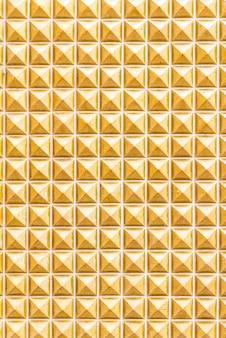 背景の黄色の大理石のタイル壁のテクスチャ