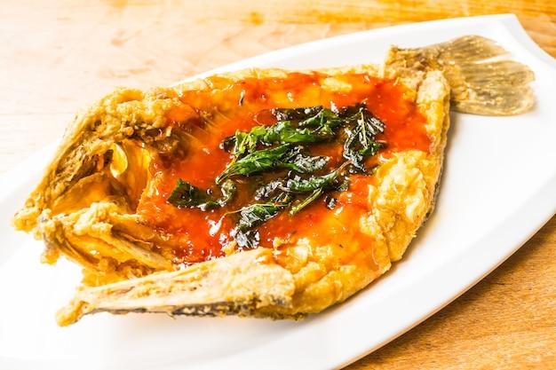 Жареная рыба сибас в белой тарелке с острым и сладким соусом