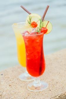 ビーチと海のガラスを飲みながらアイスカクテル