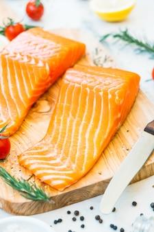 生と新鮮なサーモンの肉の切り身、木製のまな板