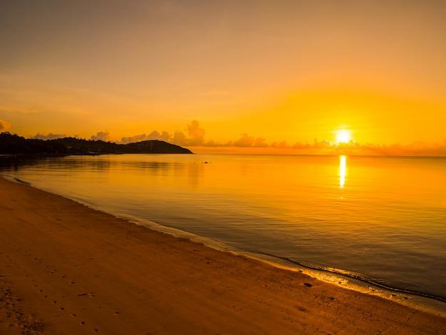 日の出や日没の時間で雲と空と美しい熱帯のビーチと海の海の風景