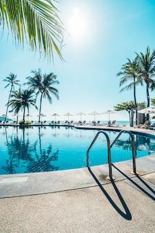 美しい熱帯のビーチと海の傘とスイミングプールの周りの椅子