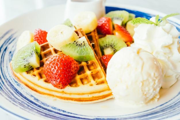 Смешанные фрукты поверх блинов и мороженого