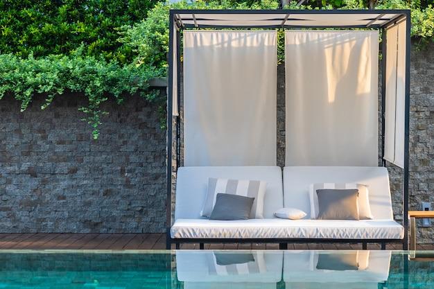 Открытый бассейн с зонтиком и креслом для отдыха.
