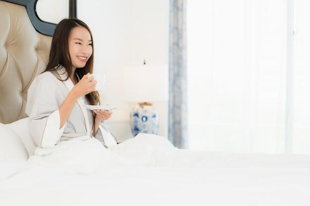 Женщина портрета красивая молодая азиатская просыпается с счастливой улыбкой и кофейной чашкой на кровати в интерьере спальни