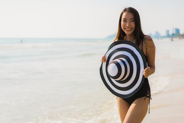 肖像画美しい若いアジア女性幸せとビーチと海に笑顔