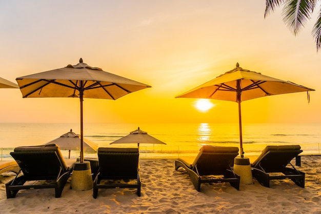 Зонтик и кресло на прекрасном пляже и море во время восхода солнца для путешествий и отдыха