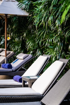 Красивый открытый бассейн с шезлонгом и зонтиком на курорте для путешествий и отдыха