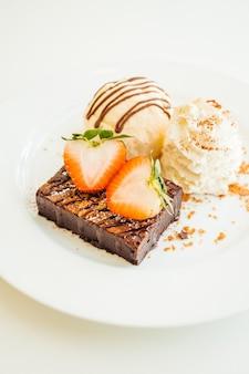 バニラアイスクリームとチョコレートブラウニーケーキの上にイチゴ