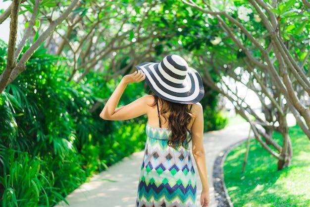 Улыбка женщины портрета красивая молодая азиатская и счастливая вокруг открытого сада