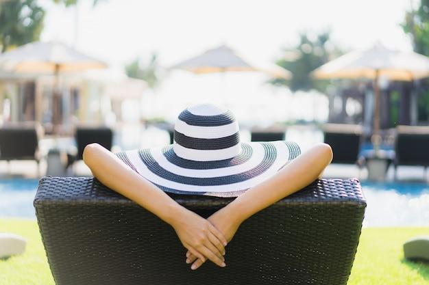 アジアの美しい若い女性の幸せな笑顔を肖像画し、ホテルのリゾートのプールの周りリラックス