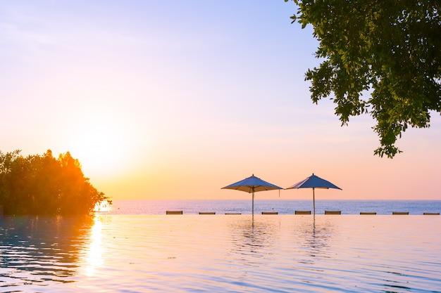 Красивый ландшафтный открытый бассейн с зонтиком и шезлонгом на курорте отеля для отдыха