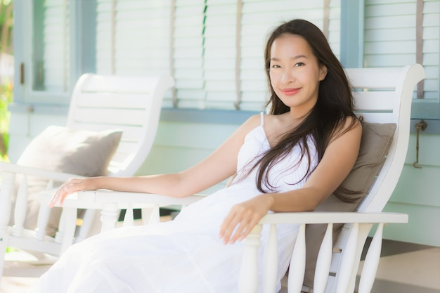 屋外パティオの周りの木製の椅子に座っている肖像画美しい若いアジア女性