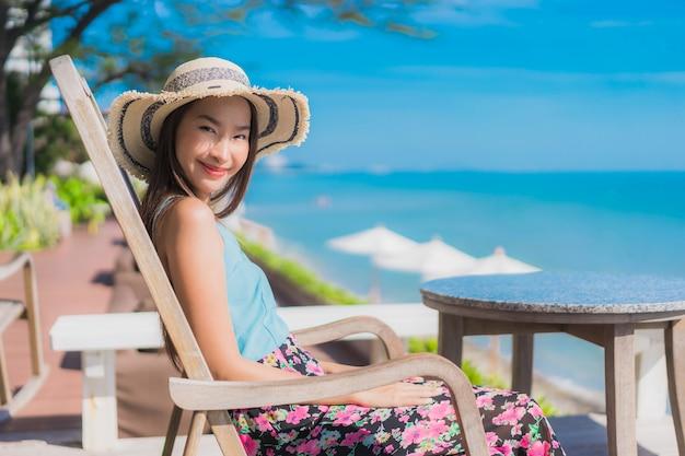 Улыбка красивой молодой азиатской женщины портрета счастливая ослабляет вокруг океана и моря пляжа