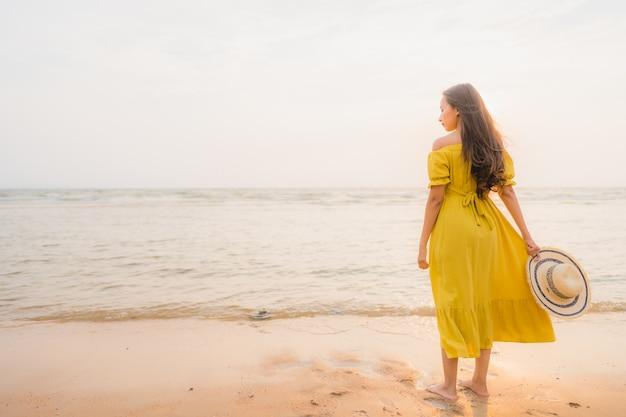 Прогулка женщины портрета красивая молодая азиатская на пляже и океане моря с улыбкой счастливой ослабляет