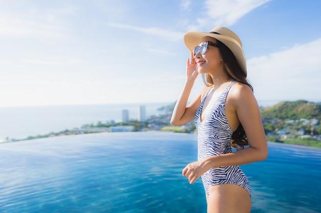 肖像画美しい若いアジア女性笑顔幸せなレジャーのためのホテルリゾートのプールの周りリラックス