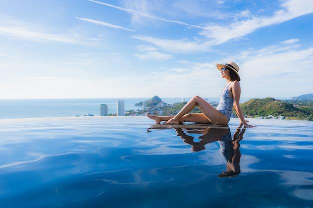 Улыбка женщины портрета красивая молодая азиатская счастливая ослабляет вокруг бассейна в курорте гостиницы для отдыха